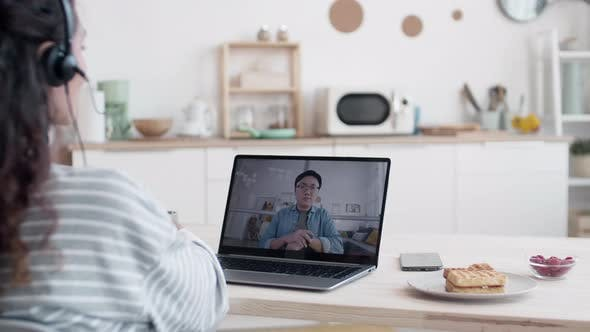 Woman Talking to Asian Colleague by Video Link