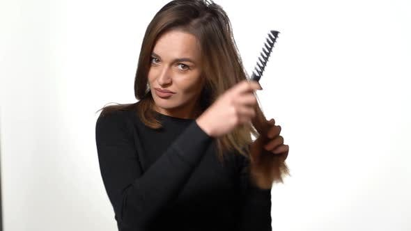 Thumbnail for Beautiful Woman in a Black Golf is Combing Her Long Hair