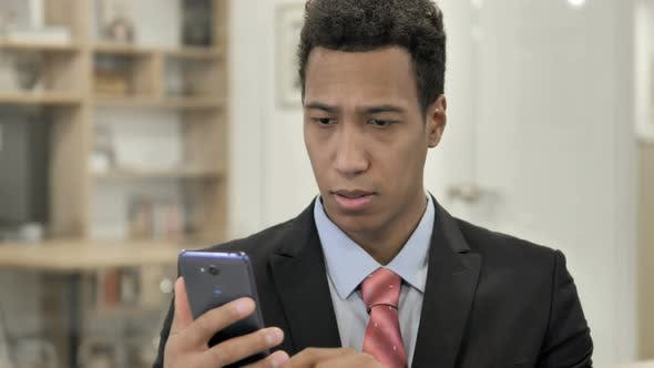 Thumbnail for African Businessman Browsing Smartphone