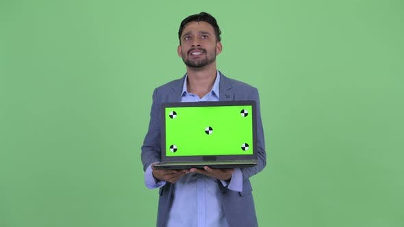 Thumbnail for Happy Young Bearded Persian Businessman Thinking While Showing Laptop