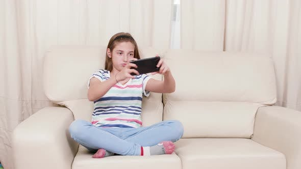 Thumbnail for Teen Girl on a Sofa Playing a Game on a Smartphone