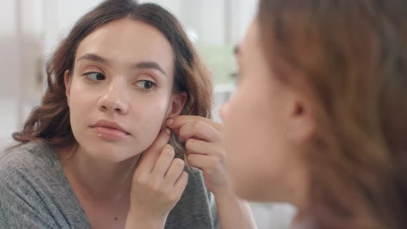 Thumbnail for Cheerful Woman Putting Earrings To Ear Looking in Bathroom Mirror at Home