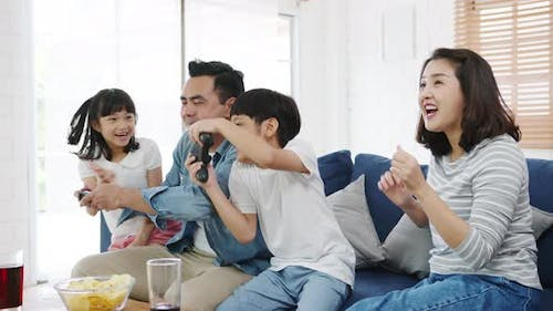 Happy Asian family funny playing video game with technology console on sofa in living room at house.
