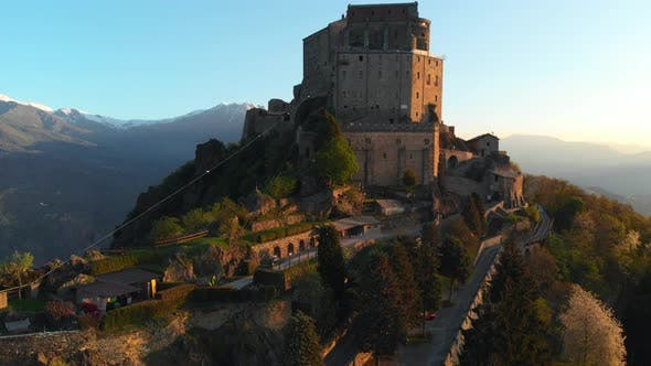 Thumbnail for Aerial: drone flying at old medieval abbey perched on mountain top at sunrise, Turin italian Alps