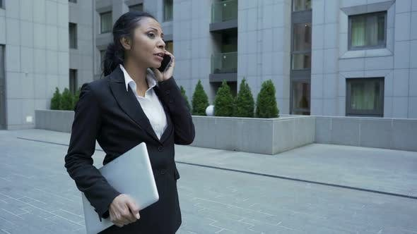 Cover Image for Lady in Business Suit with Laptop Having Informal Chat on Phone, End of Work Day
