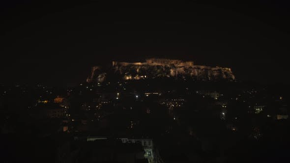 Aerial view of the parthenon temple on acropolis hill at night in Athens.