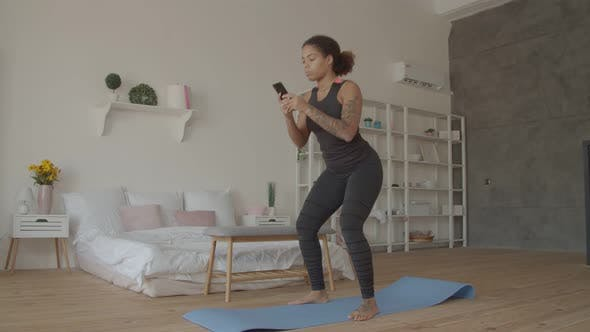 Thumbnail for African American Woman with Phone Squats at Home