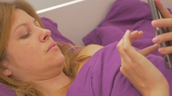 Caucasian blond woman relaxing in bed and typing messages on touch screen smart phone slow-mo 1080p