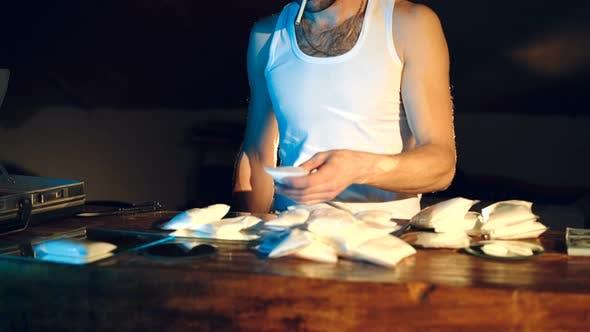 Im unterirdischen Labor legt Drogendealer Packungen mit Drogen in den Koffer
