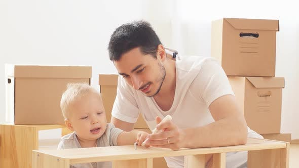 Thumbnail for Father and Son Assembling Furniture. Boy Helping His Dad at Home. Happy Family Concept