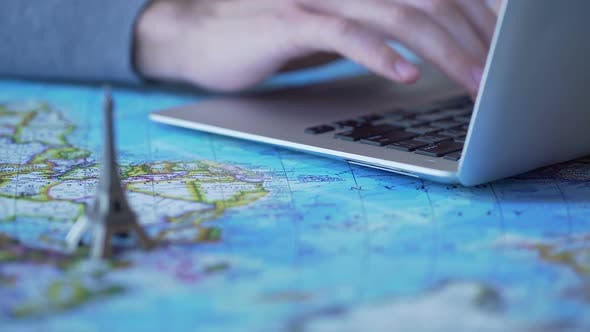 Cover Image for Tourism Blogger Posting Travel Tips, Typing on Laptop, Toy Eiffel Tower on Map