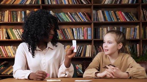 Lehrerin wiederholt Buchstaben mit junger Dame, die Karteikarten anzeigt