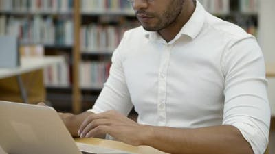 Focused African American Professor Typing on Laptop at Library