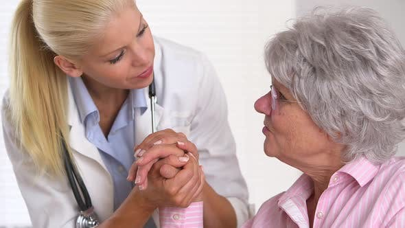 Thumbnail for Doctor holding elderly patient's had