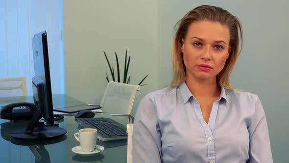 Thumbnail for A Young, Beautiful Woman Sits at a Desk in an Office and Looks at the Camera