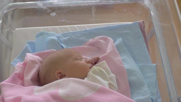 Newborn baby girl in crib being wheeled down a corridor