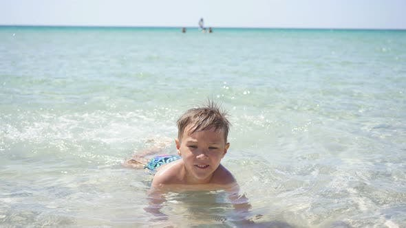 Cute Boy Learn To Swim in the Crystal Clear Sea in Shallow Water
