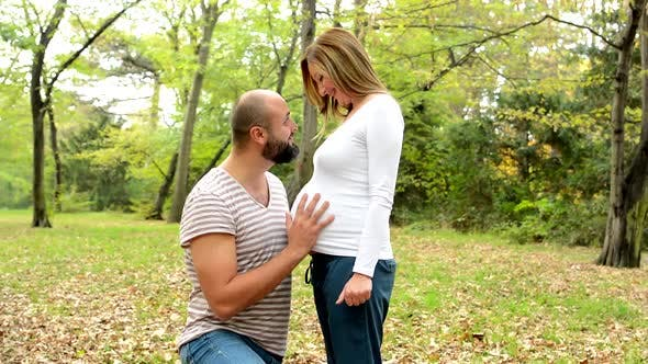 Thumbnail for Handsome Man Strokes Abdomen of a Pregnant Woman and Couple Smile Together