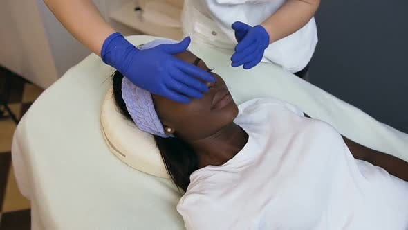 Cosmetologist Making Relaxing Massage to the Female African Client