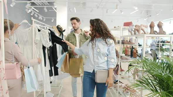 Slow Motion of Happy Shopaholic Woman Looking at Clothes While Man Carrying Bags with Purchases