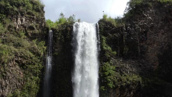 View over the top of a waterfall where the water is starting to fall down