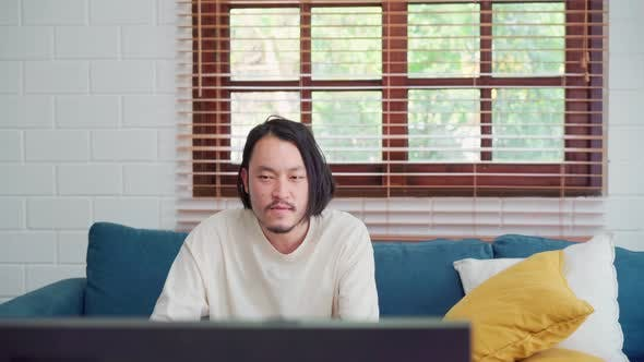 Asian man using joystick playing video games in television in living room,