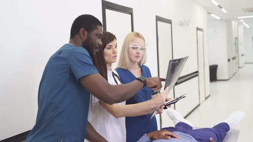 Multiracial Doctor Surgeons Examining Xray Film of Patient Head for Brain Skull Injury Emergency