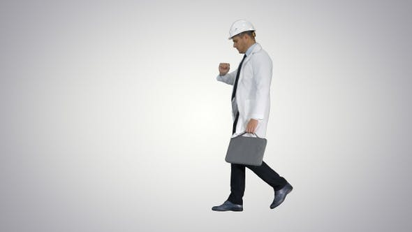 Cover Image for Engineer walking in a rush and looking at his watch on