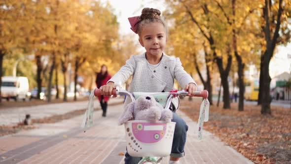 Thumbnail for Little Girl Rides Bicycle on Autumn City Boulevard