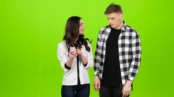Thumbnail for Loving Guy and Girl Look in the Phone and Choose Common Pictures. Green Screen