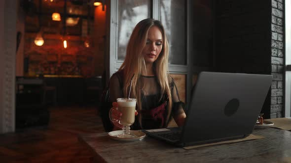 Cover Image for Side View. Young Business Woman Sitting at Table and Taking Notes in notebook.On Table Is Laptop