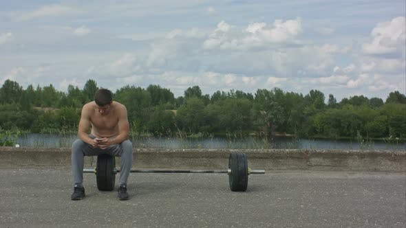 Thumbnail for Male Sportsman Using His Mobile Phone While Taking Break After Active Intense Training Outdoors