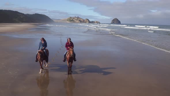 Thumbnail for Aerial view of women riding horses at beach