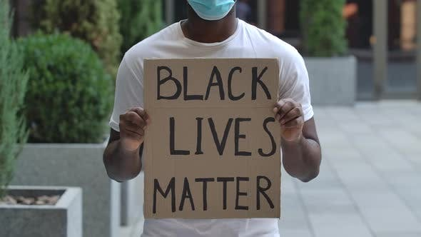 An African American Stands in the Middle of the Street Holding a Cardboard Poster in Front of Him
