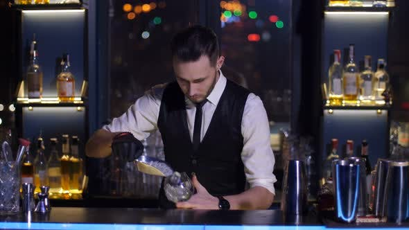 Thumbnail for Barman Putting Ice in Glass Making Cocktail at Bar