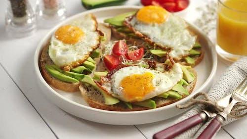 Köstliches gesundes Frühstück mit geschnittenen Avocado-Sandwiches mit Spiegelei