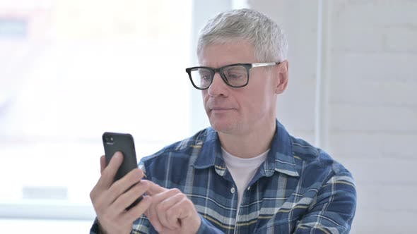 Thumbnail for Portrait of Cheerful Casual Middle Aged Man Using Smartphone