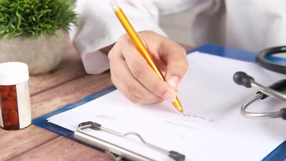 Female Doctor Hand Writing Prescription on Desk Close Up