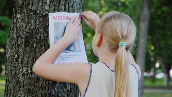 Thumbnail for Sad Girl Attaches a Missing Cat Announcement To a Tree