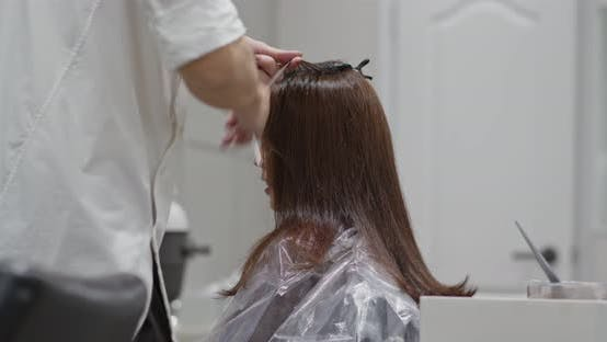 Thumbnail for Stylist hairdresser makes hair coloring