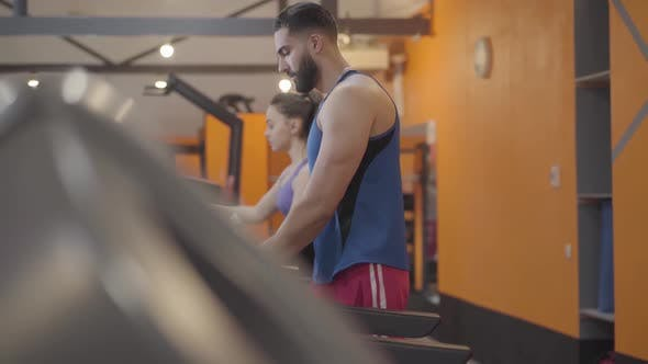 Thumbnail for Side View of Middle Eastern Man and Caucasian Woman Training on Treadmill in Gym. Serious Sportsman