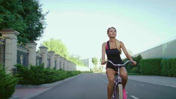 Thumbnail for Slim Woman in Sportswear Riding on Bicycle While Training in Summer Park
