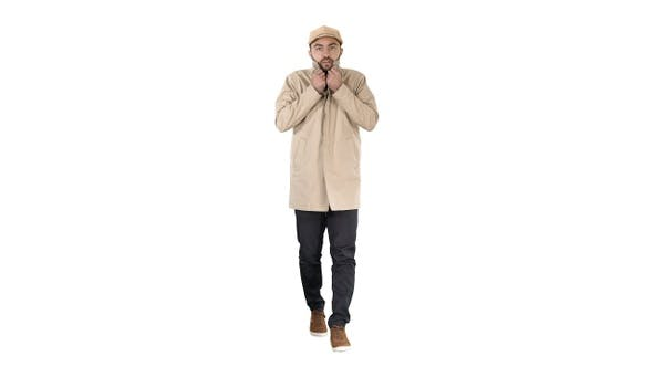 Cover Image for Young handsome man walks and buttons up cloak on white background.