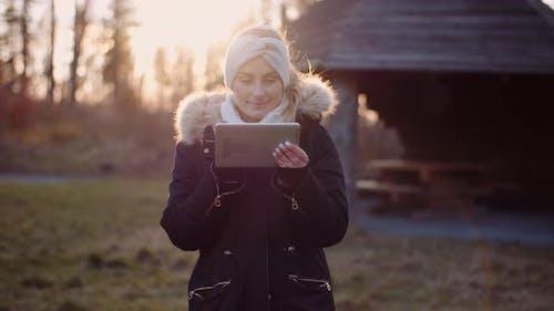 Wireless Technology - Woman Using Digital Tablet in Park in Autumn