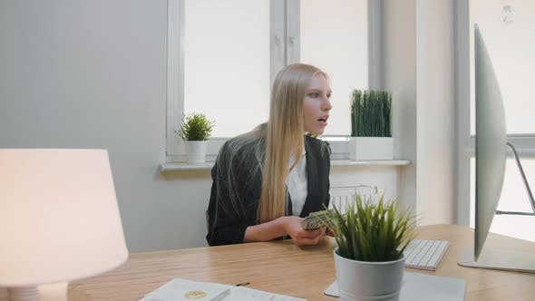 Woman Celebrating Success in Office. Elegant Blond Female Sitting at Workplace Holding in Hands