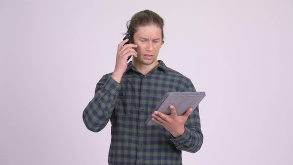 Thumbnail for Stressed Hipster Man Talking on the Phone While Using Digital Tablet