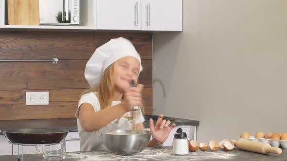 Kaukasisches kleines Mädchen versucht, selbständig in der Küche zu backen, Teig in Schüssel mischen