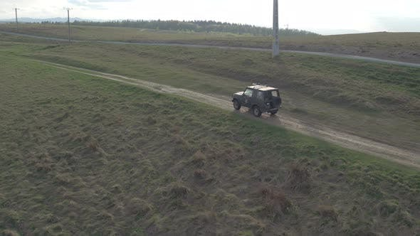 Thumbnail for Aerial view of a jeep driving on a countryside road