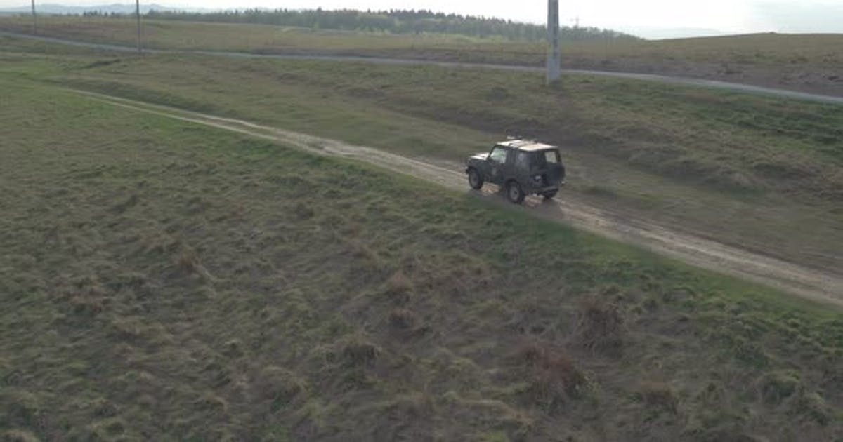 Aerial view of a jeep driving on a countryside road
