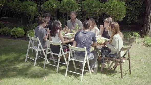 Thumbnail for Friends Gathering Around Table in Backyard